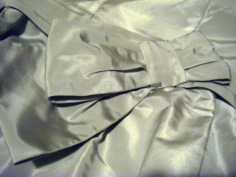 Here you can see the bow pinned to the dress.  The next step is to sew it on by hand